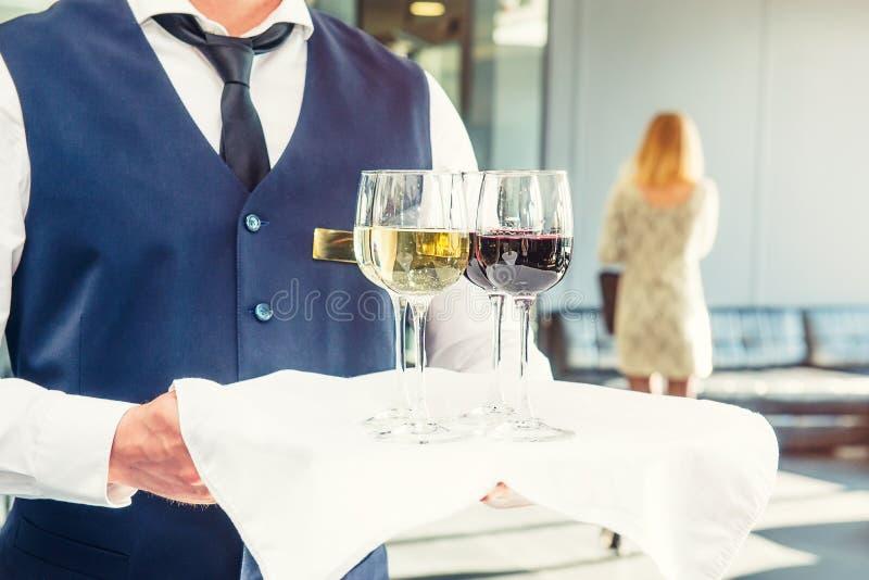 拿着有杯的制服的专业侍者一个盘子藤在企业事件 承办酒席或庆祝概念 服务在 免版税库存图片