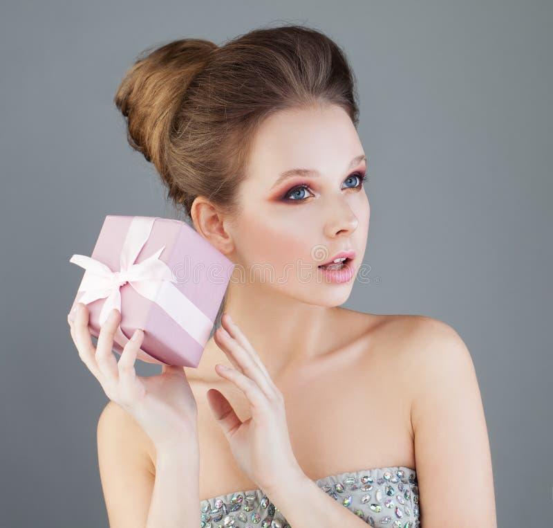 拿着有桃红色丝带的好奇妇女礼物盒 惊奇 库存图片