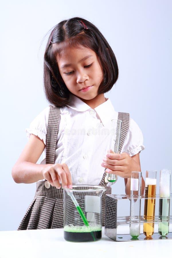 拿着有液体科学家化学和科学的小女孩试管 图库摄影
