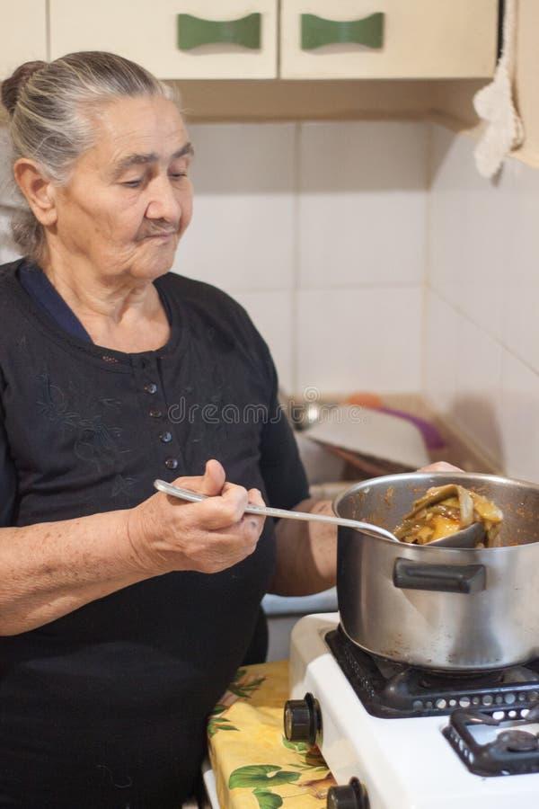 拿着有煮熟的菜的更老的古板的妇女一个杓子在罐上 库存图片