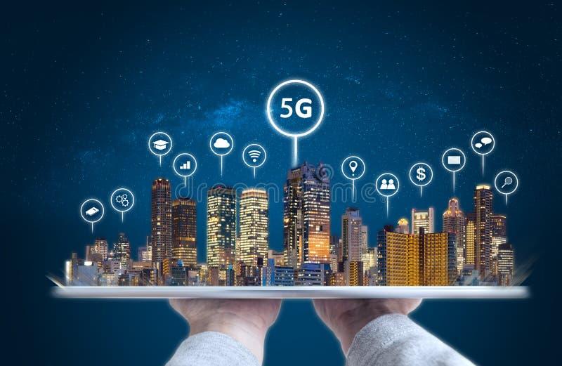 拿着有现代大厦全息图和技术象的手数字片剂 聪明的城市、5g、互联网和网络technolog