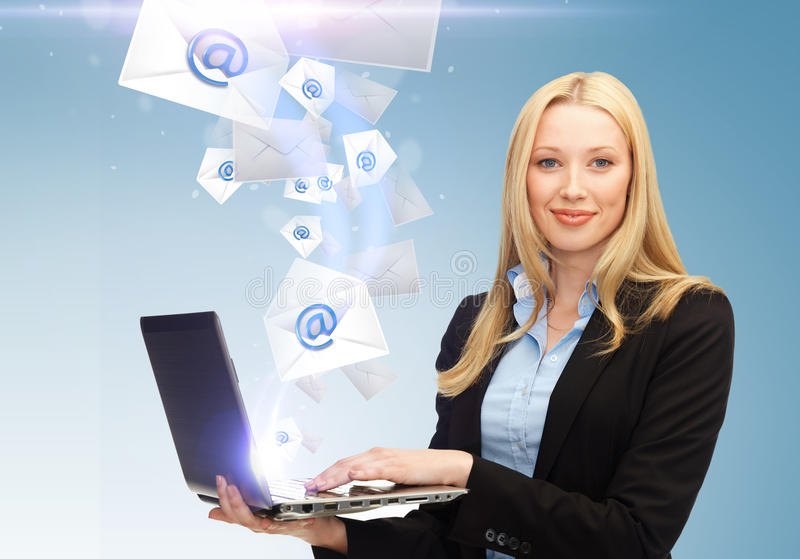 拿着有电子邮件标志的女实业家膝上型计算机 免版税库存图片
