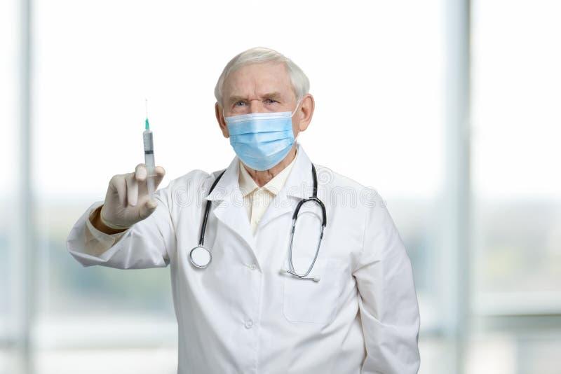拿着有疫苗的老严肃的医生注射器 免版税图库摄影