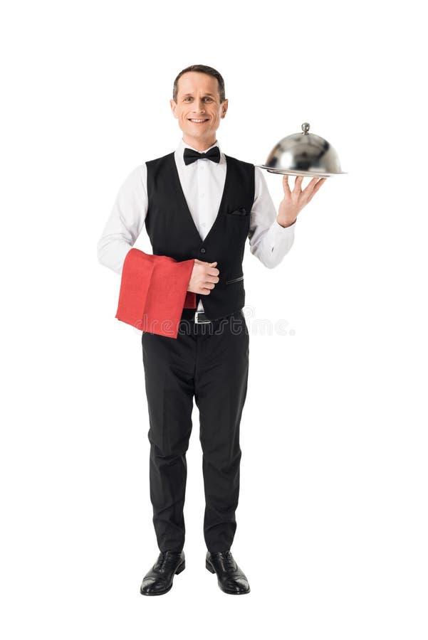 拿着有盖子的微笑的专业侍者服务盘子 免版税图库摄影