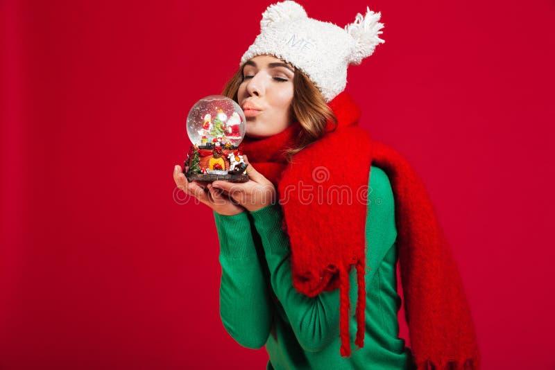 拿着有眼睛的美丽的妇女圣诞节玩具结束了亲吻 库存图片