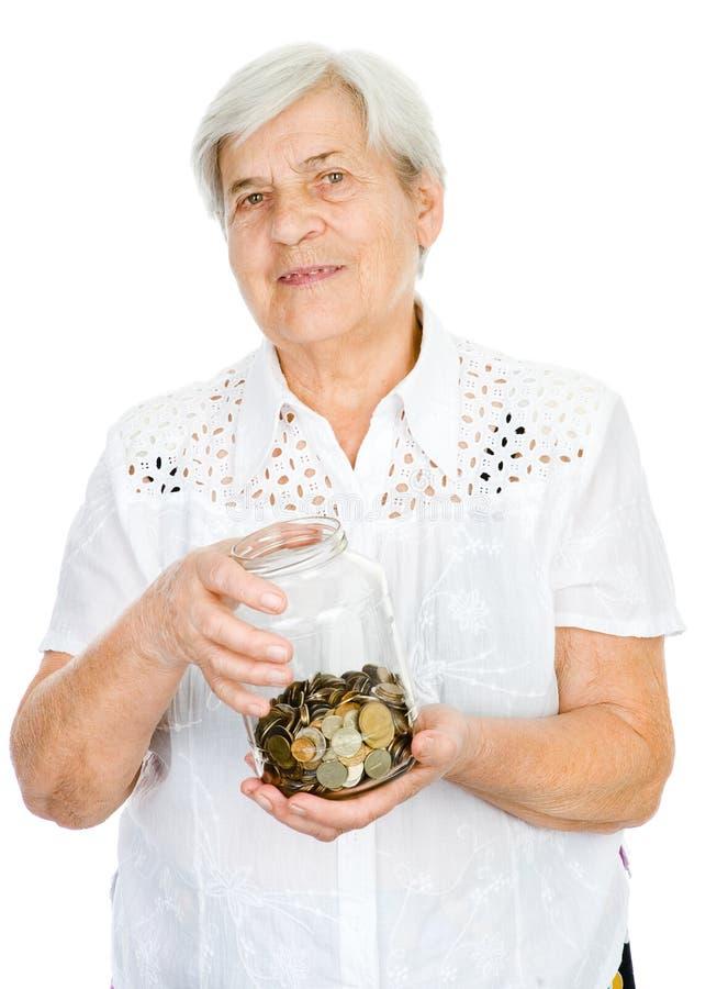 拿着有硬币的资深妇女手瓶子 免版税库存照片