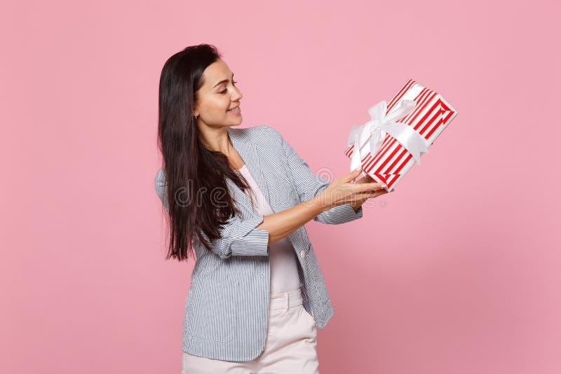 拿着有礼物丝带的微笑的年轻女人红色镶边当前箱子隔绝在桃红色淡色背景 St华伦泰` s 免版税库存照片