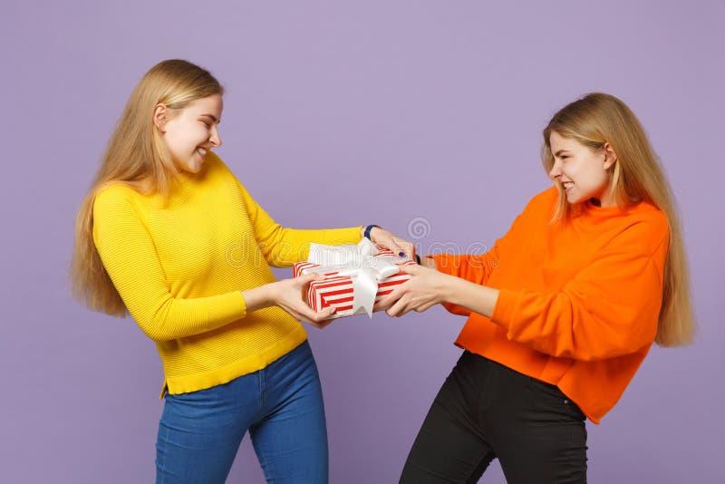 拿着有礼物丝带的生动的衣裳的两个疯狂的白肤金发的孪生姐妹女孩红色镶边当前箱子被隔绝  免版税库存照片