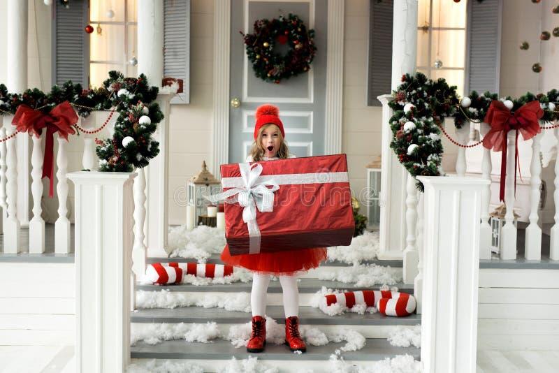 拿着有礼物的愉快的女孩一个大箱子 圣诞节和人概念 免版税库存图片