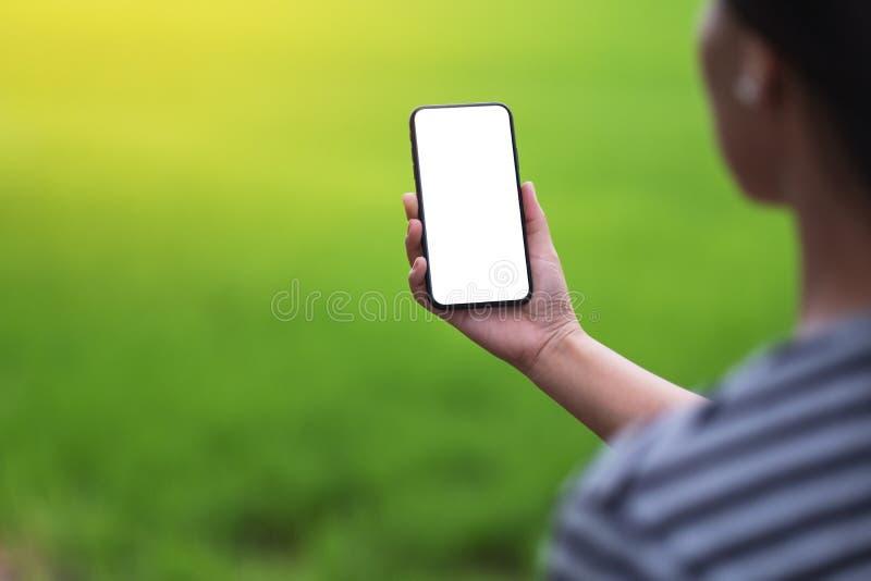 拿着有空白的桌面屏幕的妇女黑手机有迷离绿色自然背景 免版税图库摄影