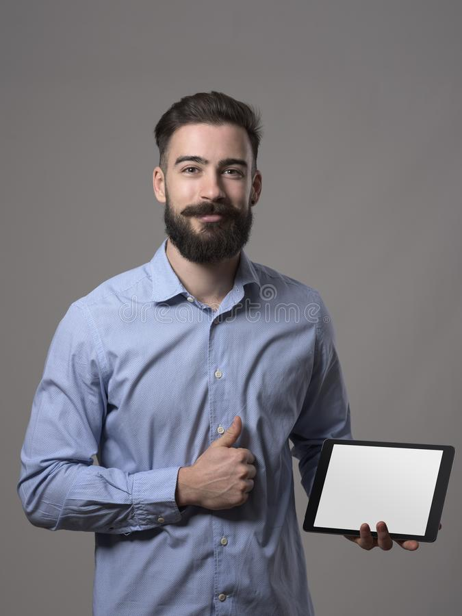 拿着有空白的白色屏幕的愉快的骄傲的成功的有胡子的人片剂做赞许认同姿态 免版税库存图片