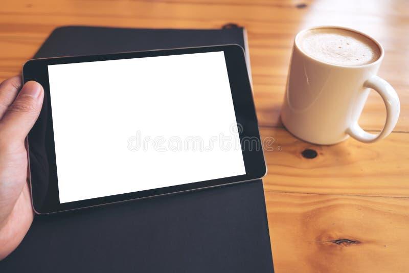 拿着有空白的白色屏幕的手的大模型图象黑片剂个人计算机在葡萄酒木桌上的一个黑纸和加奶咖啡杯子 免版税库存图片