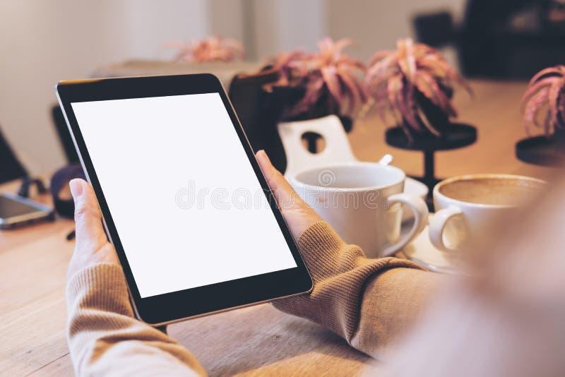 拿着有空白的白色屏幕的手黑片剂个人计算机有在木桌上的咖啡杯的在现代咖啡馆 免版税库存照片