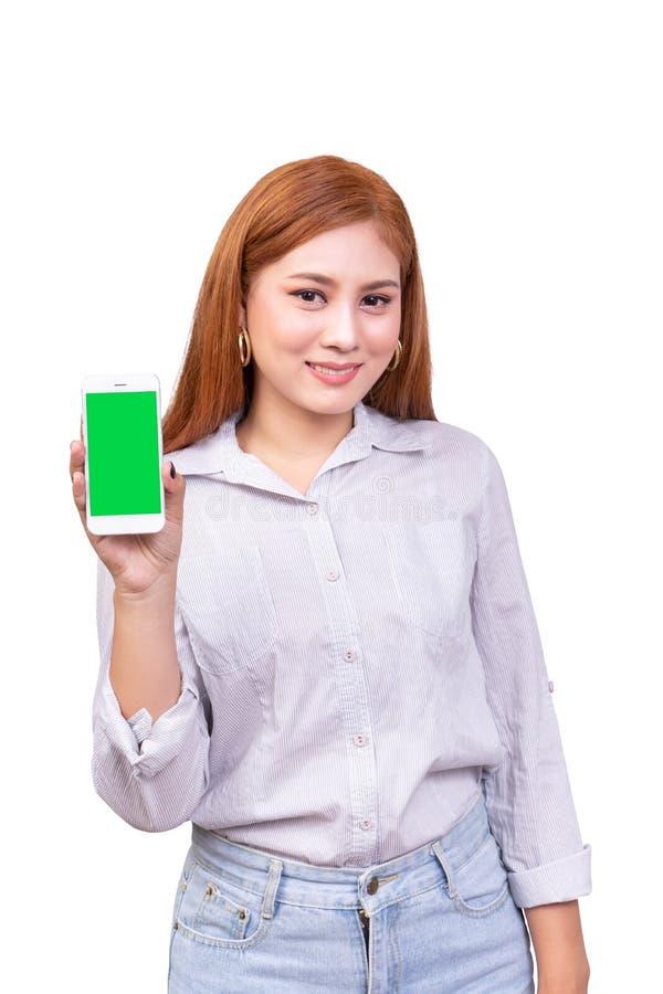 拿着有空白的绿色屏幕身分的微笑的亚裔妇女流动智能手机在白色背景,裁减路线 免版税库存照片