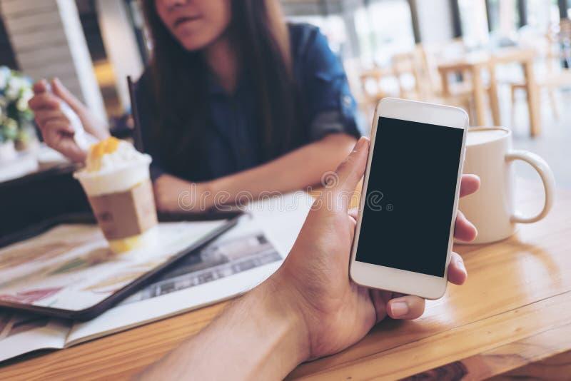 拿着有空白的黑屏幕的人` s手的大模型图象白色手机在现代咖啡馆和迷离妇女读书报纸 免版税库存图片