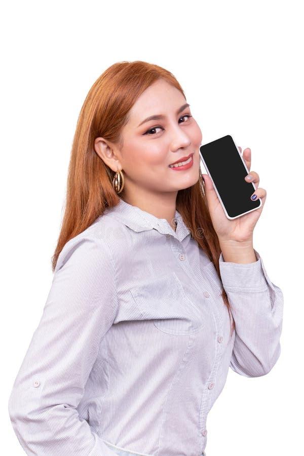 拿着有空白的黑屏幕身分的微笑的亚裔妇女流动智能手机在白色背景,裁减路线包括 库存图片