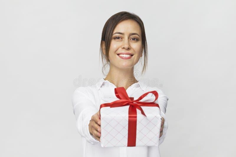 拿着有红色丝带的美丽的妇女一个礼物盒 背景查出的白色 库存图片