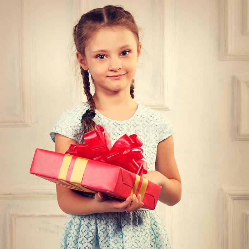 拿着有红色丝带的b的美丽的微笑的孩子女孩当前箱子 库存图片