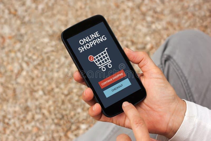 拿着有网上购物概念的手巧妙的电话在屏幕上 免版税库存图片