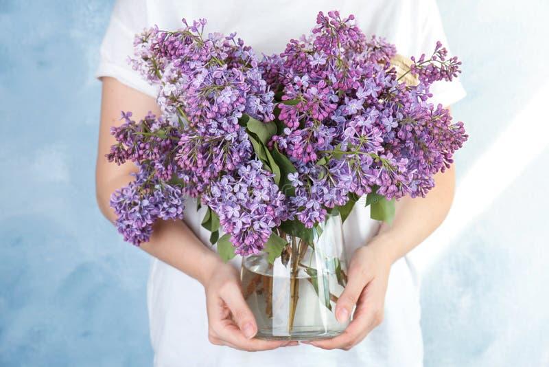 拿着有美丽的开花的丁香的少妇花瓶 库存照片