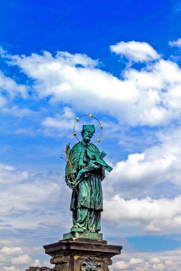 拿着有耶稣基督的Nepomuk圣约翰雕象耶稣受难象查理大桥的在布拉格 图库摄影