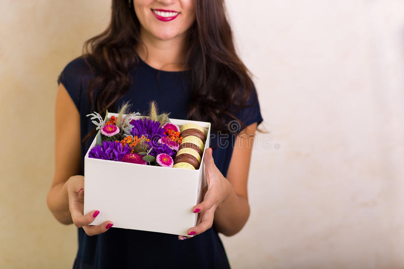 拿着有花和蛋白杏仁饼干曲奇饼的妇女一个箱子 库存照片