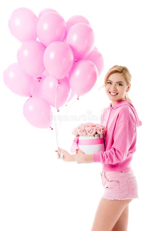 拿着有花的桃红色衣裳的白肤金发的妇女气球 免版税库存照片