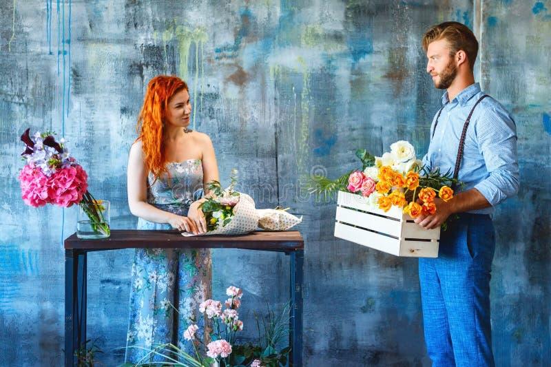 拿着有花的男性卖花人木箱在蓝色背景给红色头发妇女女性带来了交付花 免版税库存图片