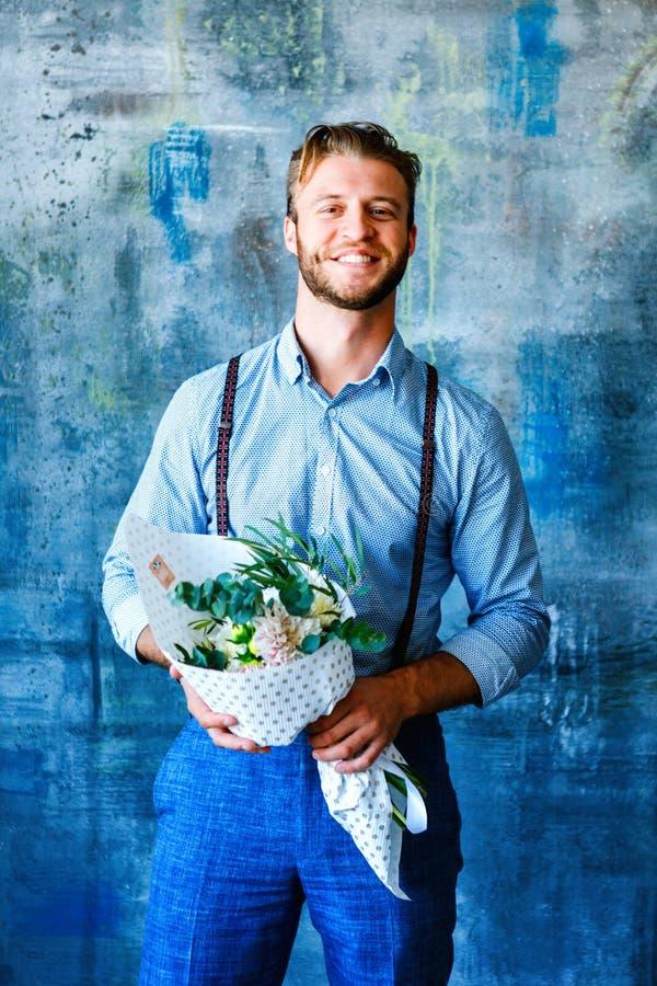 拿着有花的男性卖花人木箱在蓝色背景 库存图片