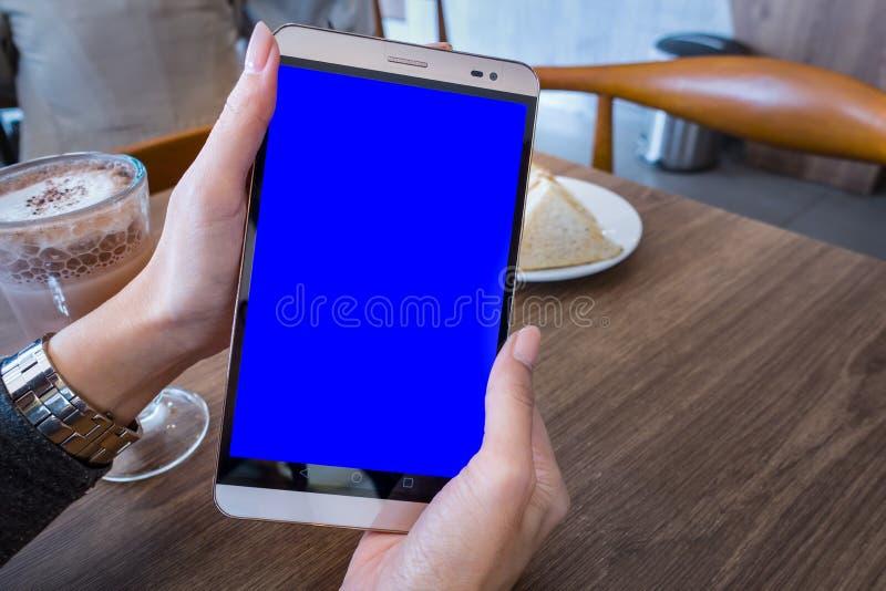 拿着有蓝色屏幕的妇女手手机片剂adve的 库存图片
