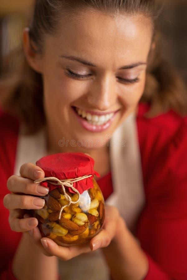 拿着有蜂蜜坚果的愉快的年轻主妇瓶子 免版税库存照片