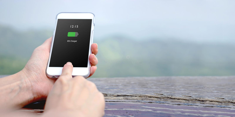 拿着有被充电的电池的女性手手机 免版税库存照片