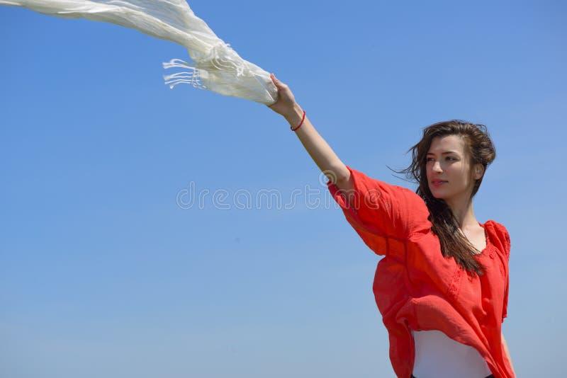 拿着有被张开的胳膊的愉快的少妇白色围巾表达自由,反对蓝天的室外射击 库存照片