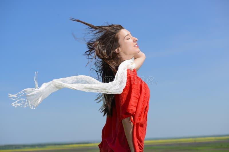 拿着有被张开的胳膊的愉快的少妇白色围巾表达自由,反对蓝天的室外射击 免版税图库摄影