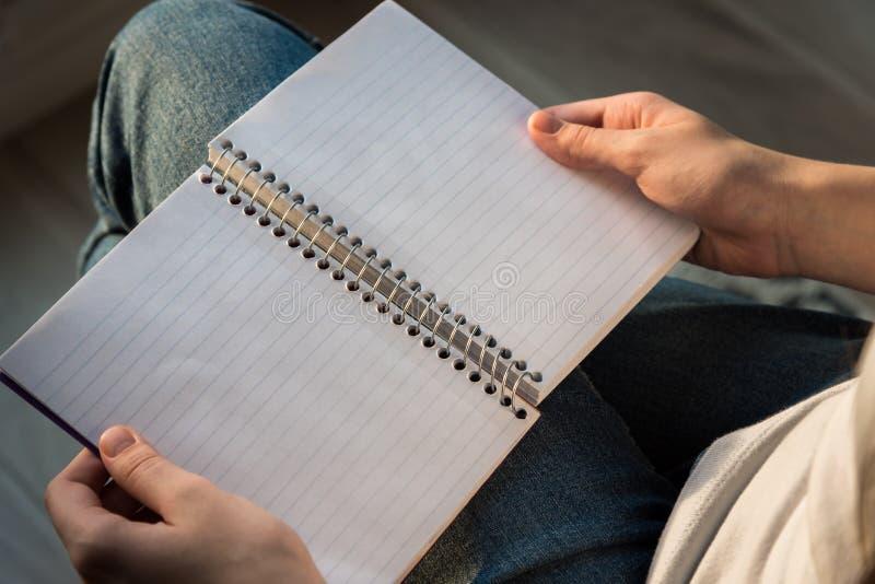 拿着有被排行的纸的妇女螺旋装订的笔记本在膝部,坐在阳光下 免版税库存图片