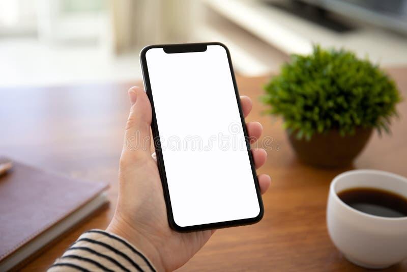 拿着有被隔绝的屏幕的女性手接触电话在桌上在办公室 免版税库存图片