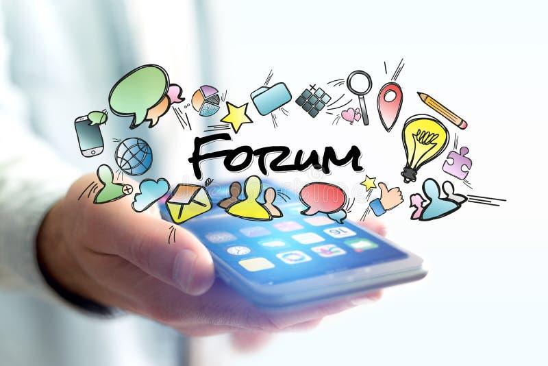 拿着有论坛标题和multimedi的人的概念智能手机 免版税图库摄影