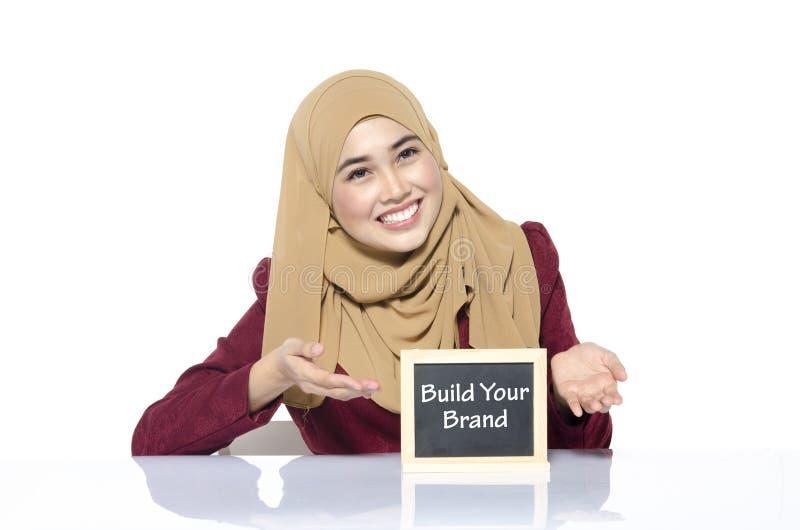 拿着有词的修造的愉快的面孔妇女黑板您的品牌 免版税库存图片