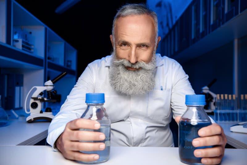 拿着有试剂的瓶和看照相机的狡猾科学家在实验室 库存照片