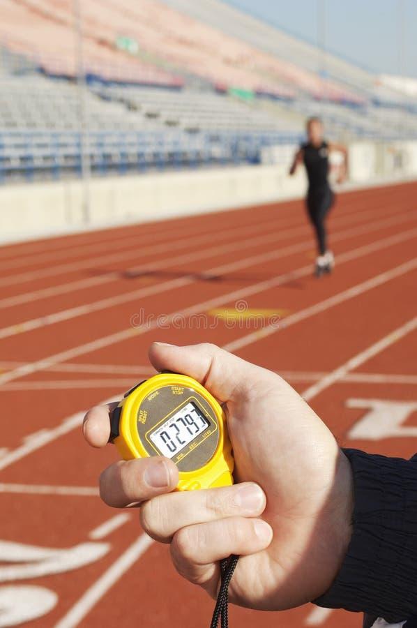 拿着有赛跑者的手秒表在赛马跑道 库存照片