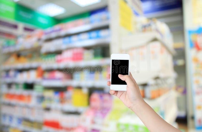 拿着有超级市场的手巧妙的电话 免版税库存照片