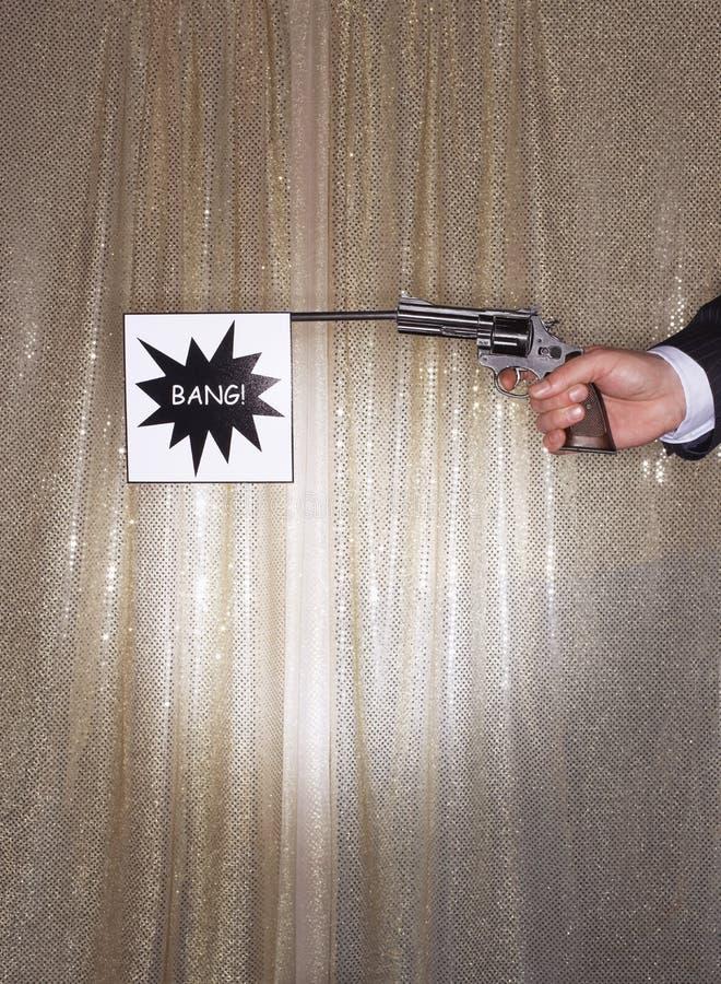 拿着有轰隆旗子的手手枪 图库摄影