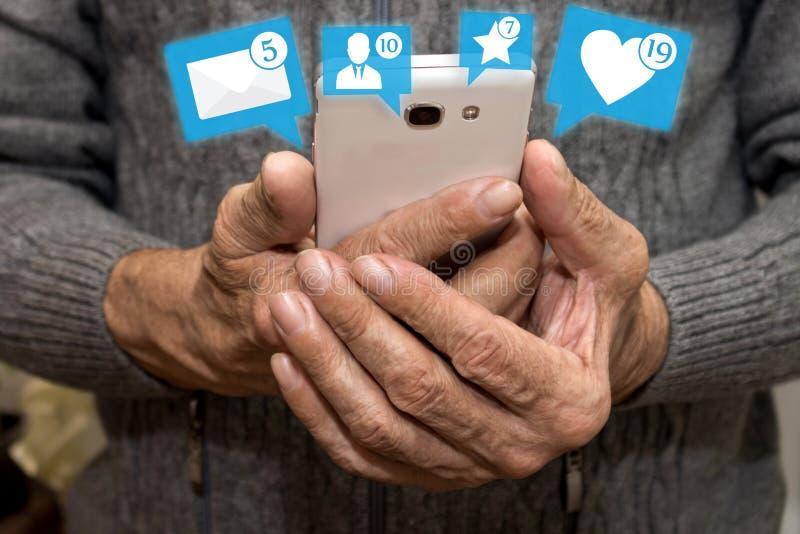 拿着有通知象的年长人智能手机从社会媒介的 年长概念的社会媒介 充满爱的闲谈 免版税库存照片