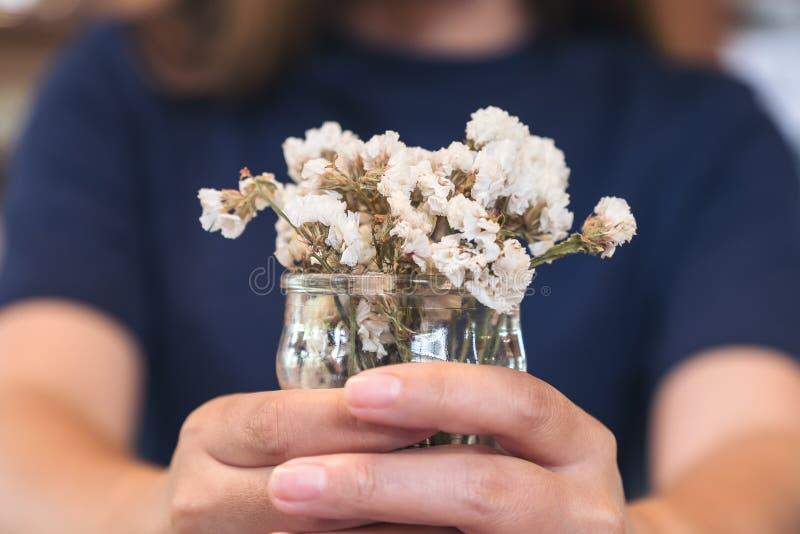 拿着有里面白花的妇女一个花瓶 免版税库存图片