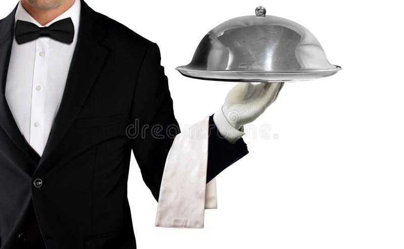 拿着有金属钓钟形女帽和餐巾的无尾礼服的侍者服务的盘子 免版税库存图片