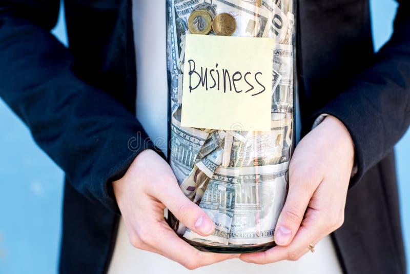 拿着有金钱的女实业家一个瓶 免版税图库摄影