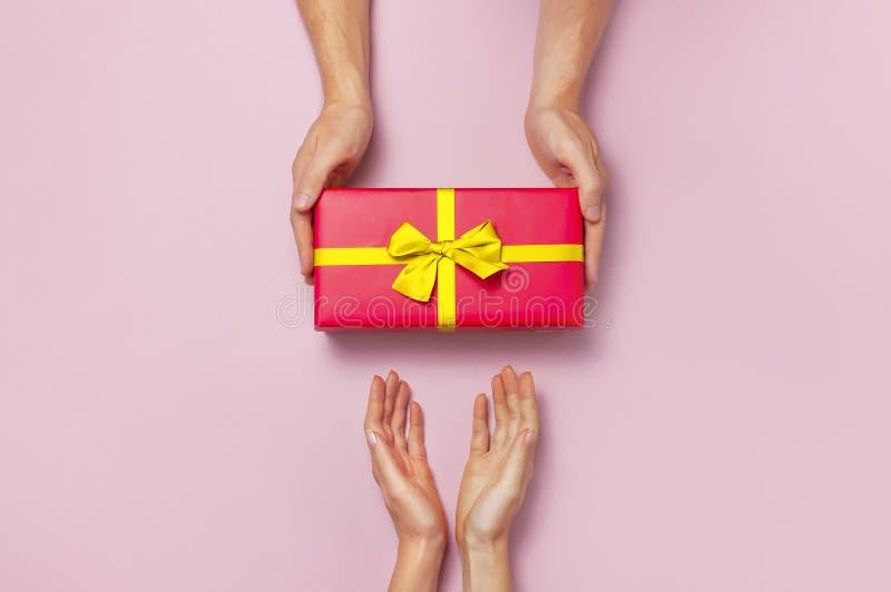 拿着有金黄丝带的男性和女性手顶视图红色礼物盒在桃红色背景平的位置 礼物为生日,valen 免版税库存照片