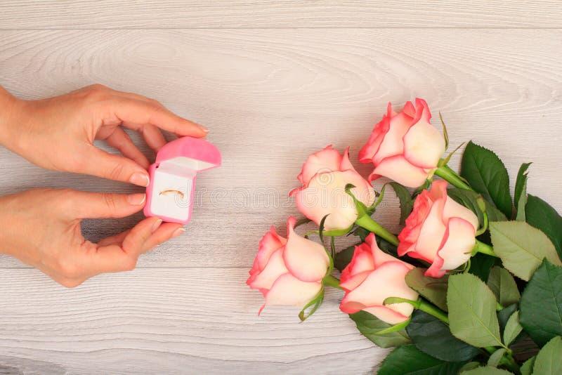 拿着有金黄圆环的妇女一个箱子在有花的手上在背景 免版税库存图片