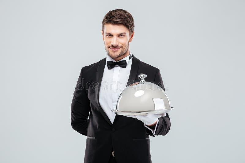 拿着有银色承办酒席圆顶的微笑的年轻男管家盘子 库存照片