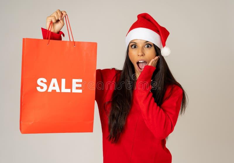 拿着有销售的圣诞老人帽子的妇女圣诞节购物带来写对此看起来激发和愉快 库存照片